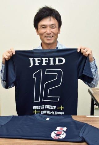日本代表公式応援Tシャツを持ち、支援を呼び掛ける西眞一監督=姶良市役所