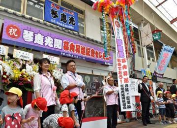 園児らとくす玉を割って琴恵光関の入幕を祝う両親(左の2人)と後援会関係者=25日午前、延岡市の山下新天街