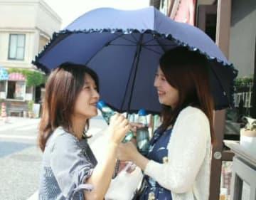 今年初の猛暑日となった日田市。散策をしながら冷たいラムネを飲んで涼む観光客=25日午後