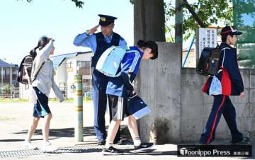 下校する児童らを見守る署員ら=25日午後2時50分ごろ、青森市の甲田小学校前