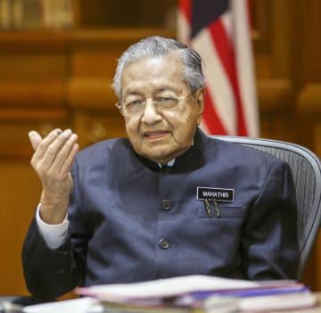 26日、マレーシアのクアラルンプール近郊の首相府で会見するマハティール首相(共同)