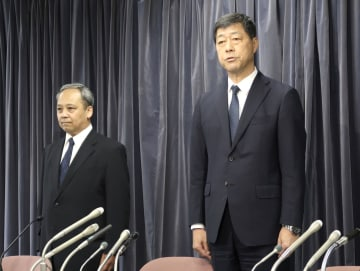 記者会見で謝罪するプリンスホテルの小山正彦社長(右)ら=26日午後、国交省