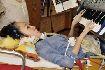 ベッドに据え付けた電子楽器のキーボードを演奏する奥本涼楓さん=26日午後、北海道函館市
