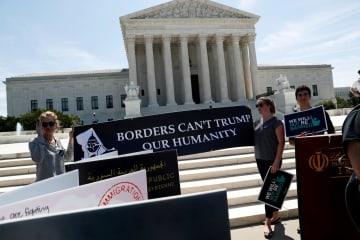 26日、米ワシントンの最高裁前で、トランプ政権の移民政策に抗議する横断幕を掲げる人たち(ロイター=共同)