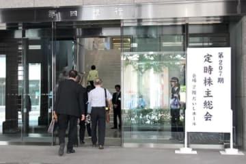 第四銀行の株主総会の会場に入る株主ら=26日、新潟市中央区の第四銀本店