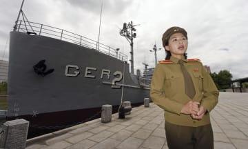 北朝鮮の首都平壌で、1968年に北朝鮮が拿捕した米情報収集船「プエブロ号」の前で話す案内役の金美京さん=15日(共同)