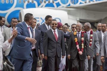 26日、エチオピア・アディスアベバの空港で、アビー首相(中央)の出迎えを受けるエリトリアのオスマン外相(中央右)ら(AP=共同)