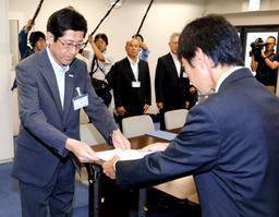 長田淳教育長(左)に申し入れ書を手渡すPTA会長の男性=神戸市役所