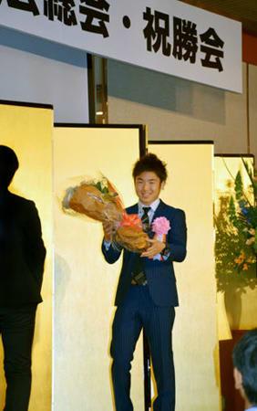 地元後援会が主催した祝勝会で花束を受け取る拳四朗(京都市内のホテル)