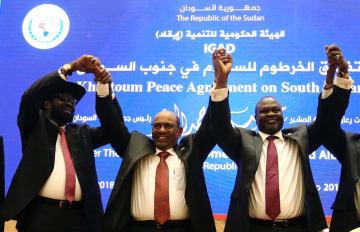 南スーダン内戦の和平合意後に手をつないで喜ぶキール大統領(左)とマシャール前第1副大統領(右)ら=27日、スーダン・ハルツーム(ロイター=共同)
