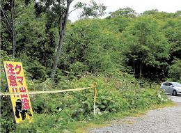 クマに襲われた可能性がある遺体が23日に見つかった現場近くには規制線が張られ注意喚起の看板も設置された=26日、仙北市田沢湖玉川