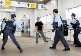 駅での無差別テロ対応訓練で犯人役を取り囲む警察官
