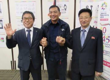 南北合同チームの結成が決まり、手を取り合う(左から)韓国、大会組織委、北朝鮮の関係者=28日、ジャカルタ(OCA提供・共同)