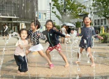 水遊びを楽しむ子どもたち=28日、JR大分駅