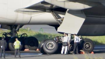 誘導路上で停止した大韓航空機の右主脚(手前)周辺を調べる関係者=29日午後5時40分ごろ、成田空港