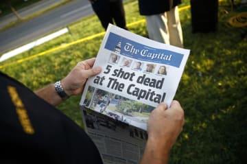 29日、米メリーランド州アナポリスで、新聞社キャピタル・ガゼットで起きた銃撃事件を報じる同社の新聞(AP=共同)