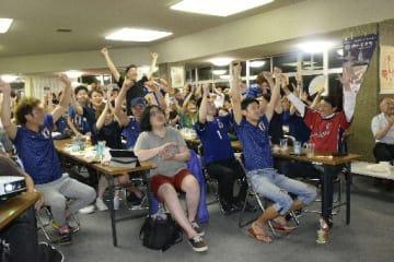 日本代表の予選リーグ突破に喜びを爆発させる野辺地町のファン=29日午前0時55分ごろ、野辺地町中央公民館