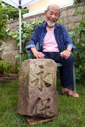 掘り返された親柱を見て笑顔を見せる三崎嘉禧さん=芦屋市松浜町