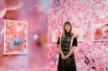 会場に立つ写真家・映画監督の蜷川実花さん。床と壁に桜の写真が貼られている=熊本市現代美術館