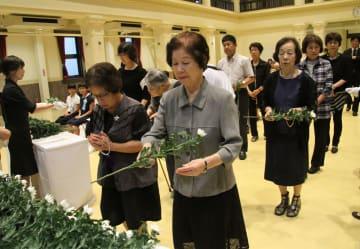 犠牲者の冥福を祈り、花を手向ける参列者=佐世保市民文化ホール