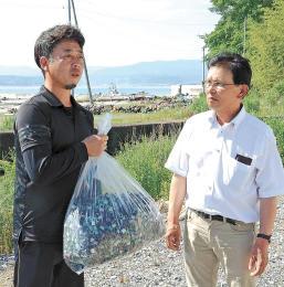 貴田さん(右)から豆管を受け取った菅原さん