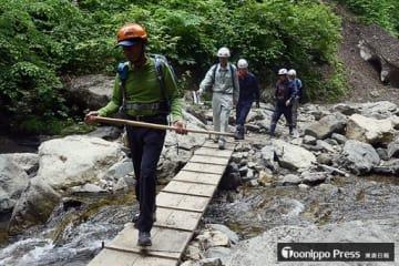 「暗門渓谷ルート」の途中に設けられた木板を渡る参加者たち