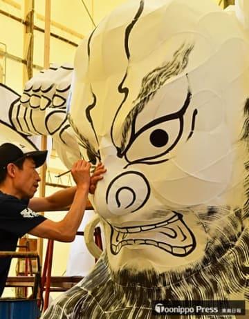 大型ねぶたの面の書き割りで、慎重に筆を進める京野さん=30日午後、青森市安方のラッセランド