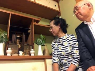 自宅で預かることになった牛頭天王像を見つめる上原さん夫妻(京都市下京区)