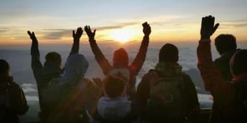 山開きを迎えた富士山の山頂で、御来光に向かって万歳する登山客=1日朝