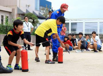消火器の使い方を訓練する子どもたち=長崎市立高城台小