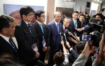 審議終了後、報道陣に喜びを語る中村知事(中央)ら=バーレーン、マナマ市内のホテル