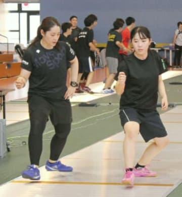 代表選手(左)からアドバイスを受けながら動きを確認する参加者=大分市