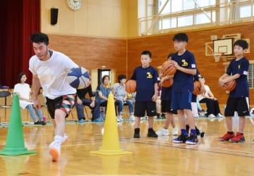 ドリブルを実演する山本吉昭さん(左)。遠隔指導で児童の技術向上を目指す