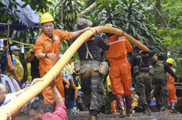 排水ホースを洞窟内に引く、救助隊のメンバー=2日、タイ北部チェンライ(共同)