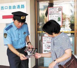 チラシを配り容疑者に関する情報提供を呼び掛ける警察官=1日午後0時15分ごろ、盛岡市のJR盛岡駅