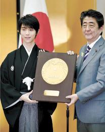 国民栄誉賞授与式で、安倍首相(右)から盾を受け取るフィギュアスケート男子の羽生選手=2日午前、首相官邸