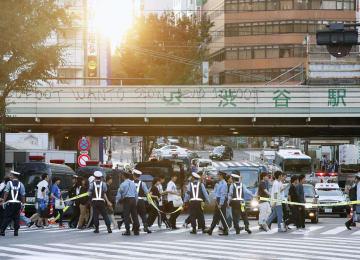 日本が敗戦し、警察官に誘導されながら東京・渋谷の交差点を渡るサポーターら=3日早朝