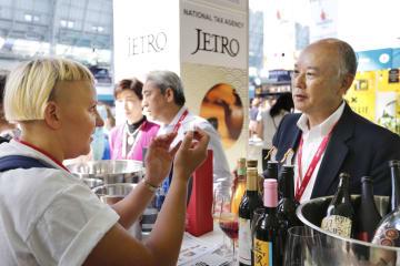 酒類見本市「インバイブ・ライブ」で、日本のワインを試飲し担当者に質問する来場者(左)=2日、ロンドン(共同)