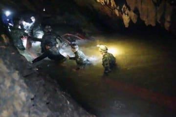 2日、タイ北部チェンライ郊外の洞窟内を歩く救助チーム(タムルアン救助活動センター提供・AP=共同)