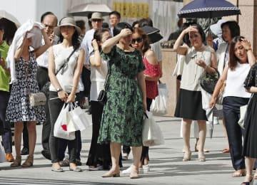 6月27日、猛暑となった東京・銀座で、強い日差しに手をかざす人たち