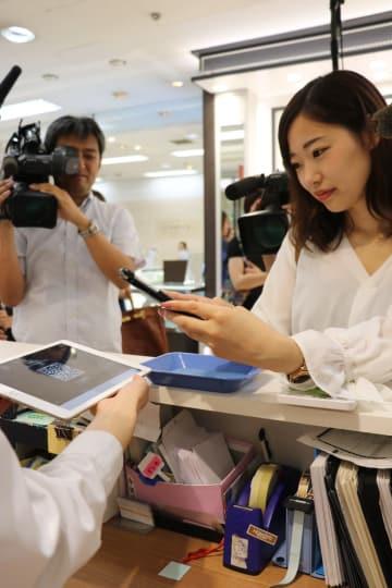 QRコードをスマートフォンで読み込んで決済する「よかペイ」=長崎市、浜屋百貨店