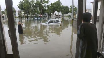 大雨の影響で冠水した道路と自宅から不安そうに見る女性=3日午前、北海道旭川市