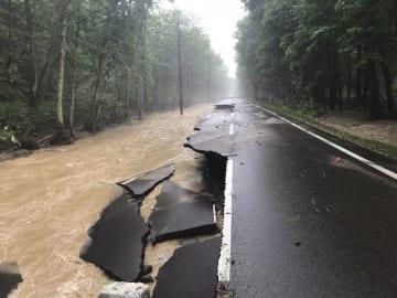 大雨の影響で大きく崩れた北海道東川町の天人峡美瑛線の道路=3日午前10時半ごろ(北海道上川総合振興局提供)