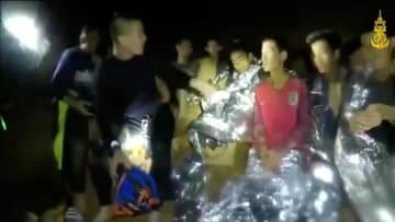 タイ北部チェンライ郊外の洞窟内で、特殊部隊の男性にあいさつするサッカーチームの少年ら=3日(タイ海軍特殊部隊提供・ロイター=共同)