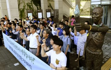 徴用工像(右)のそばで記者会見しシュプレヒコールを上げる市民団体メンバーら=4日、韓国・釜山の国立日帝強制動員歴史館(共同)