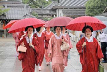 雨用のコートを着て参拝に訪れた芸舞妓ら(4日午前9時28分、京都市東山区・八坂神社)