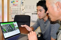 衛星データを用いた農地管理アプリについて説明する坪井俊輔さん(左)=丹波市青垣町中佐治
