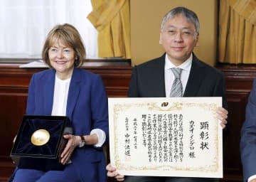 3日、ロンドンで長崎県の名誉県民称号を授与され証書を手にするカズオ・イシグロさん。左は妻ローナさん(共同)