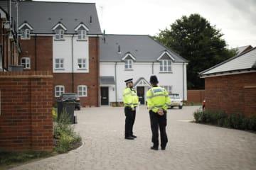 住宅で2人が重体となった事案で、現場周辺に立つ警官=4日、英南部エームズベリー(AP=共同)