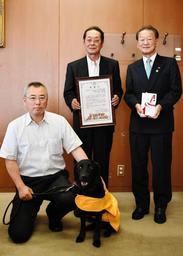 兵庫盲導犬協会に500万円を寄付した吉見淳二さん(中央)と協会の幹部=明石市中崎1、明石市役所